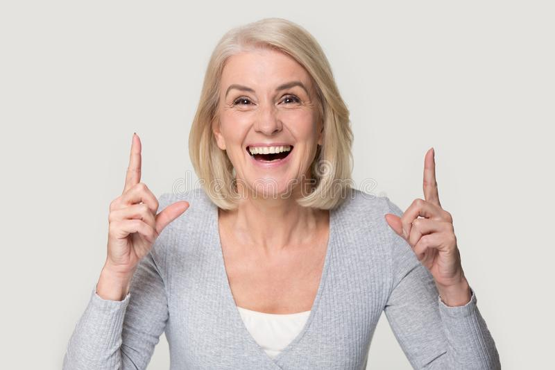 Excited senior woman point at good deal upward. Excited gray-haired aged woman isolated on grey studio background point with finger upward, smiling overjoyed stock photos