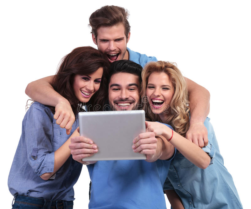 Excited group of friends reading surprising stuff on their table. T pad computer on white background stock photography