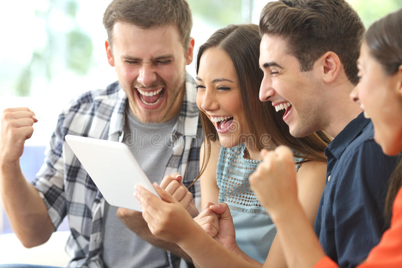 Excited group of friends watching tv from tablet stock images