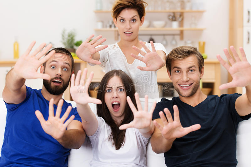 Excited group of young men and women. With smiling wide eyed expressions extending their outspread hands towards the camera royalty free stock photography
