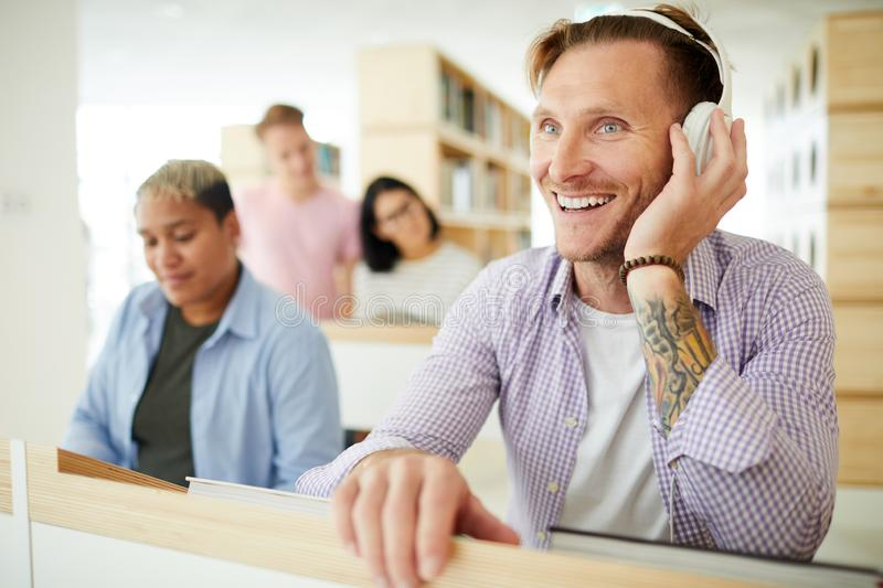 Excited guy listening to music in headphones stock photos