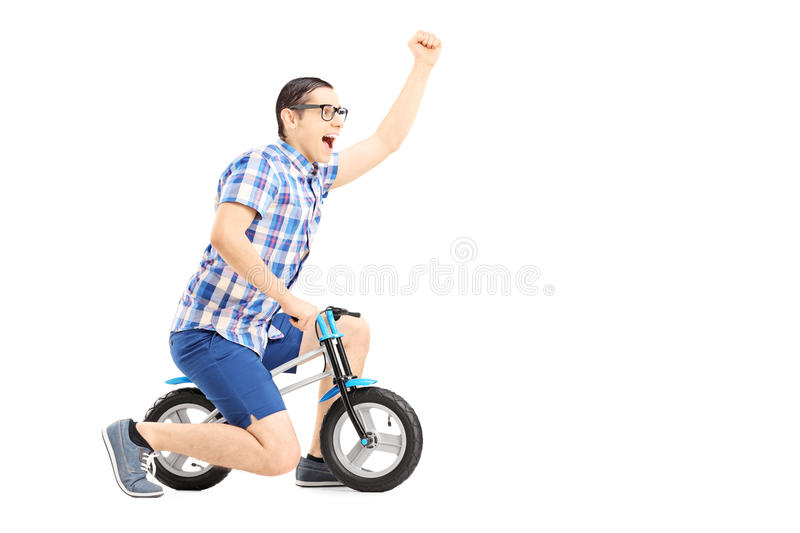 Excited Guy Riding A Small Bicycle And Gesturing Happiness Royalty Free Stock Image