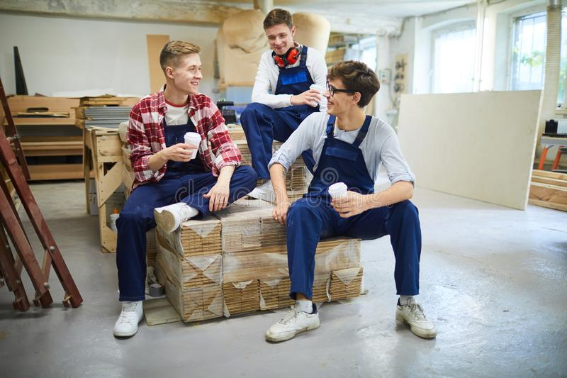 Excited guys with coffee cups communicating at break. Smiling excited young guys with coffee cups sitting on packaged wooden planks and communicating while royalty free stock photo