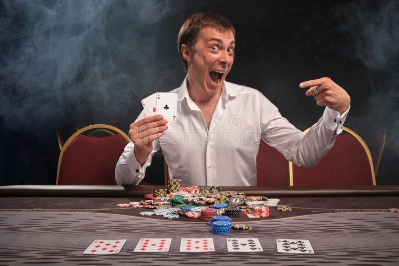 Handsome emotional man is playing poker sitting at the table in casino. stock images