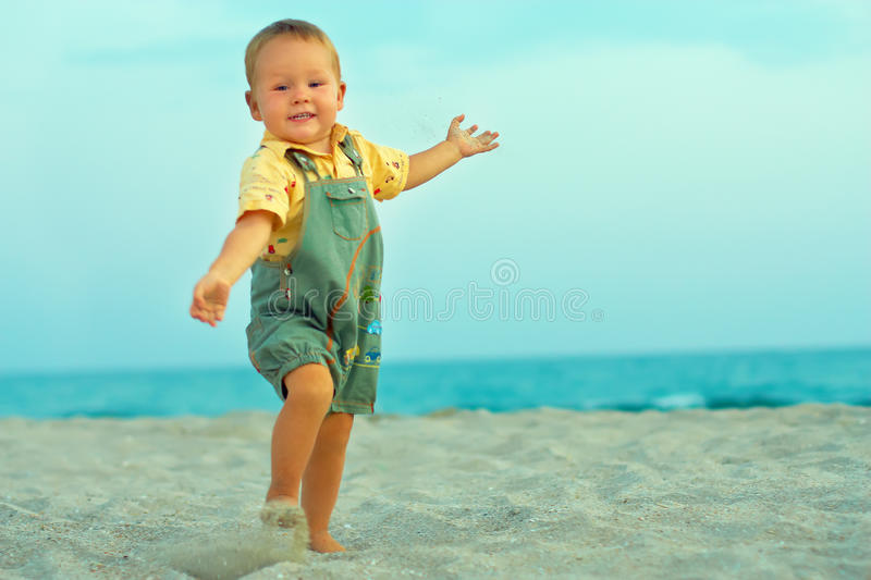 Excited happy baby boy playing on beach royalty free stock photos