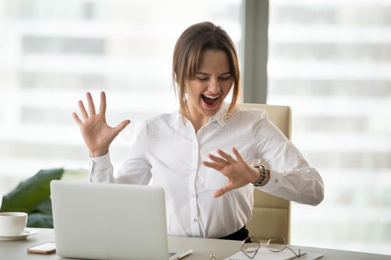 Excited happy employee looking at wristwatch satisfied with meet. Ing deadline finished work day in time, cheerful businesswoman checking time feeling motivated royalty free stock image