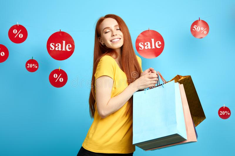 Excited happy girl with many colorful packages posing to the camera royalty free stock images