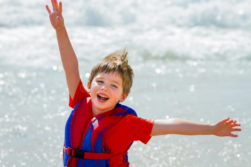Excited and Happy Little Boy With Life Jacket Playing With Arms royalty free stock photos