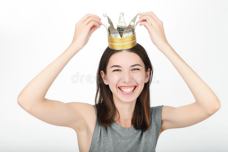 Excited happy looking woman wearing a handmade princess crown. Closeup of happy mixed race asian caucasian female model isolated o stock photography