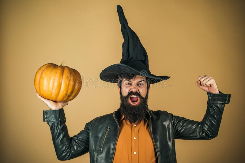 Excited happy man with pumpkin. Trick or treat. Thanksgiving seasonal cooking ingredients. Bearded man cook in Halloween. Hat with pumpkin royalty free stock photos