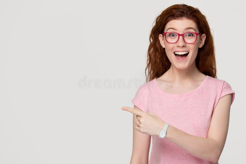 Excited happy red-haired woman customer pointing finger at copy space royalty free stock photo