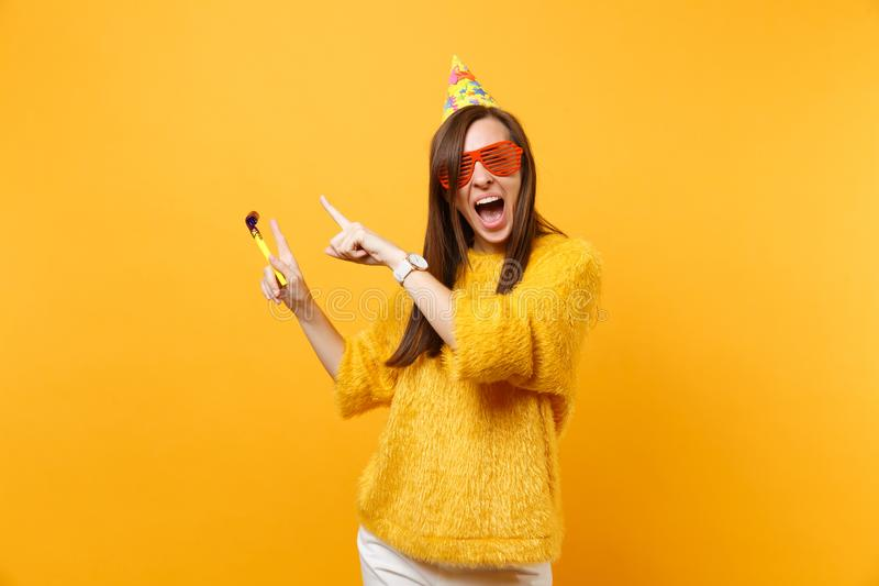 Excited happy woman in orange funny glasses, birthday hat with playing pipe pointing index fingers aside on copy space. Celebrating isolated on yellow royalty free stock images
