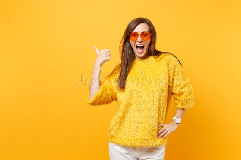 Excited happy young woman in fur sweater and heart orange glasses pointing thumb aside on copy space isolated on bright. Yellow background. People sincere royalty free stock photography