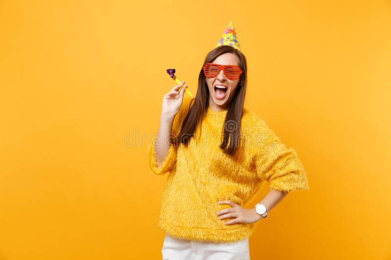 Excited happy young woman in orange funny eyeglasses birthday party hat with playing pipe celebrating isolated on bright. Yellow background. People sincere royalty free stock photography