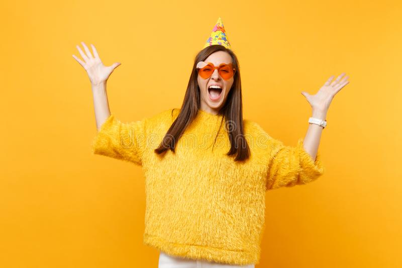 Excited happy young woman in orange heart glasses, birthday party hat spreading hands, enjoying holiday, celebrating. Isolated on bright yellow background royalty free stock image