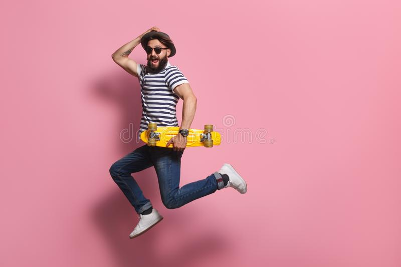 Excited hipster with skateboard jumping. Handsome male in stylish outfit holding yellow skateboard and leaping on pink background royalty free stock image