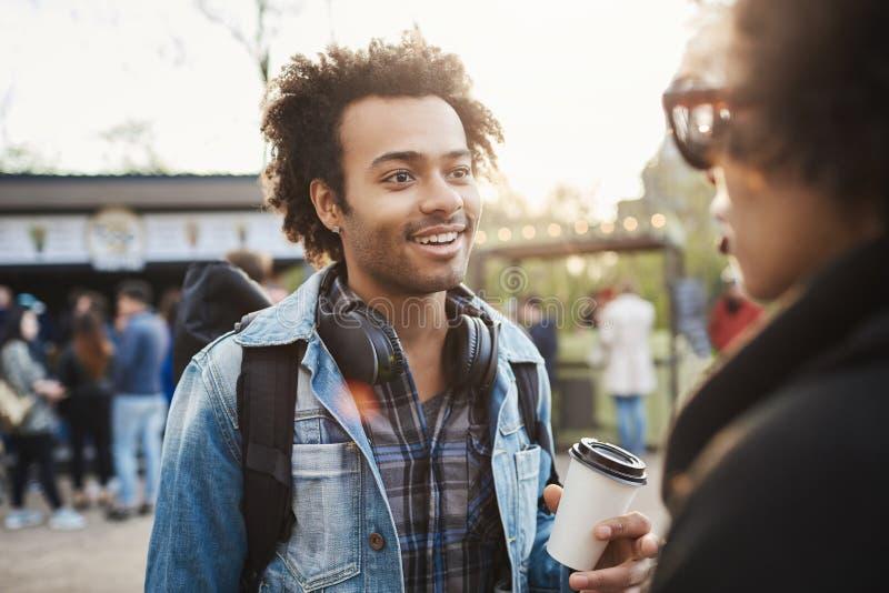 Excited i intrygujący młody afroamerykański mężczyzna opowiada z przyjacielem podczas gdy być w parku, jest ubranym modnych ubran zdjęcie stock