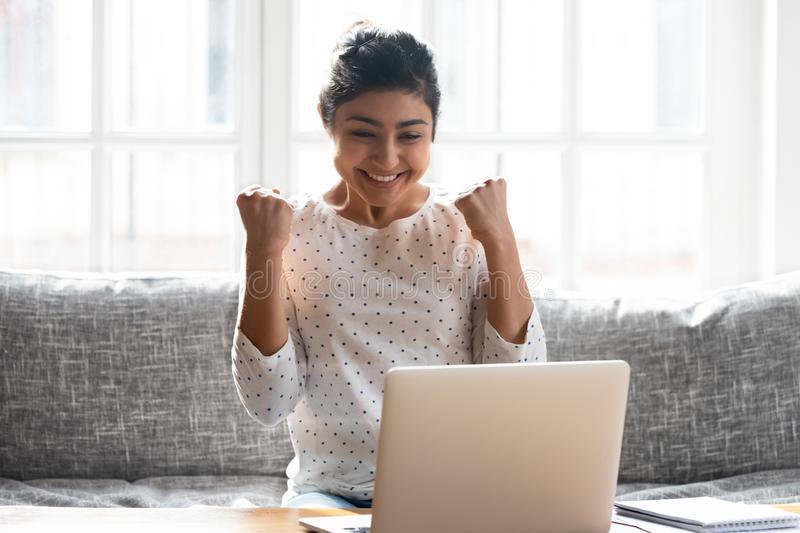 Excited Indian woman celebrating win, looking at laptop screen royalty free stock photo