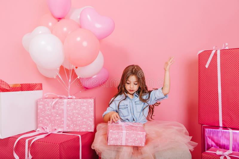 Excited joyful little girl in tulle skirt opening birthday present suround big colorful giftboxes  on pink. Background. Celebrating birthday party with balloons stock images