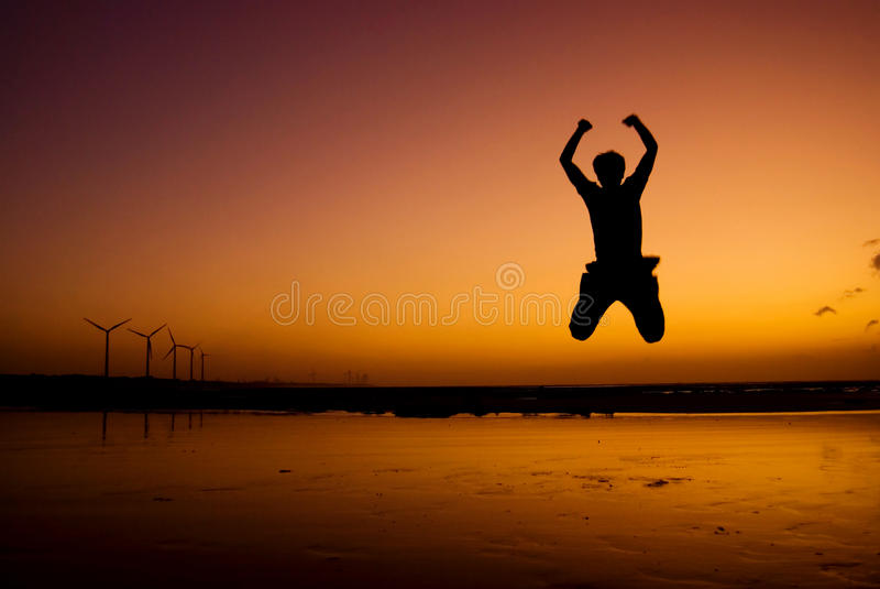 Excited Jump in the beach under sunset stock photography