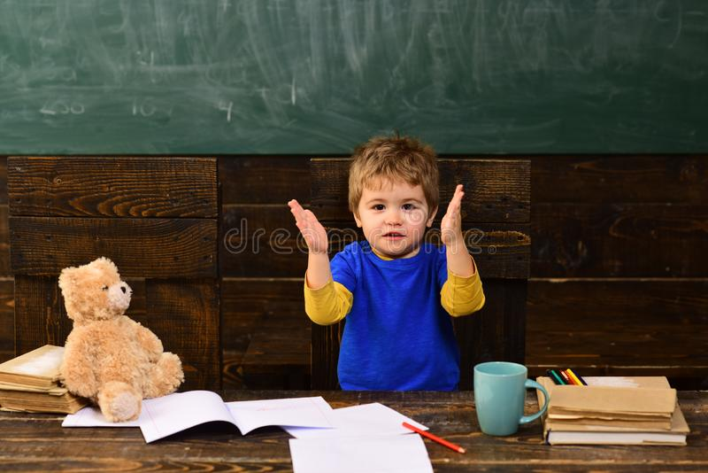 Excited kid clapping hands. Funny boy singing cheerful song. Small child in kindergarten royalty free stock photography