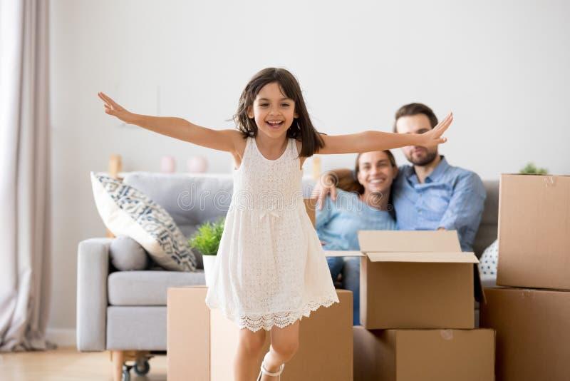 Excited kid girl running over living room enjoying moving day stock image