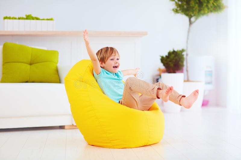 Excited kid having fun, sitting on yellow bean bag at home royalty free stock image