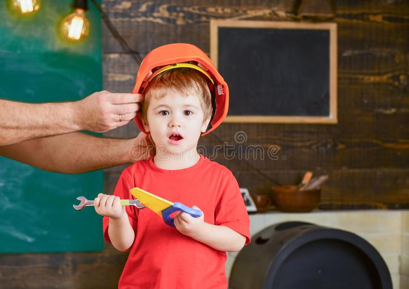 Excited kid playing with toy tools. Blond boy shouting in workshop. Daddys little helper. Male hand holding orange. Protective helmet stock images