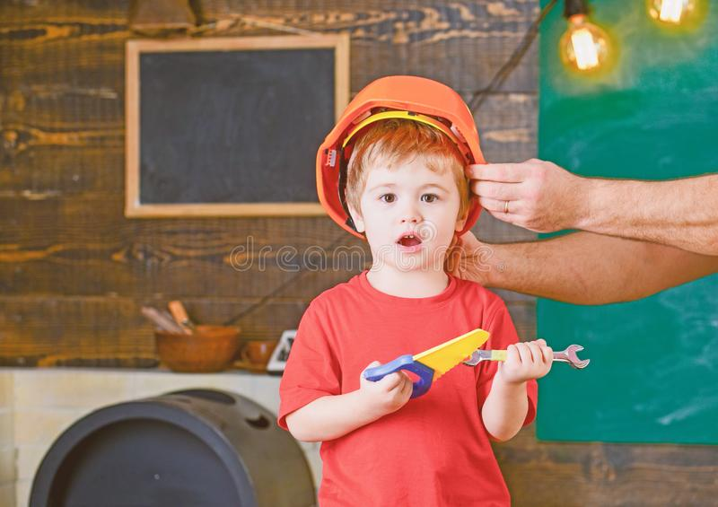 Excited kid playing with toy tools. Blond boy shouting in workshop. Daddys little helper. Male hand holding orange. Protective helmet royalty free stock images
