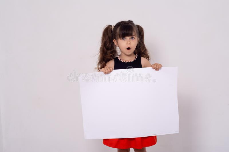 Excited kid with white template. Advertising place for you, empty card, cute kid holding it. stock photography
