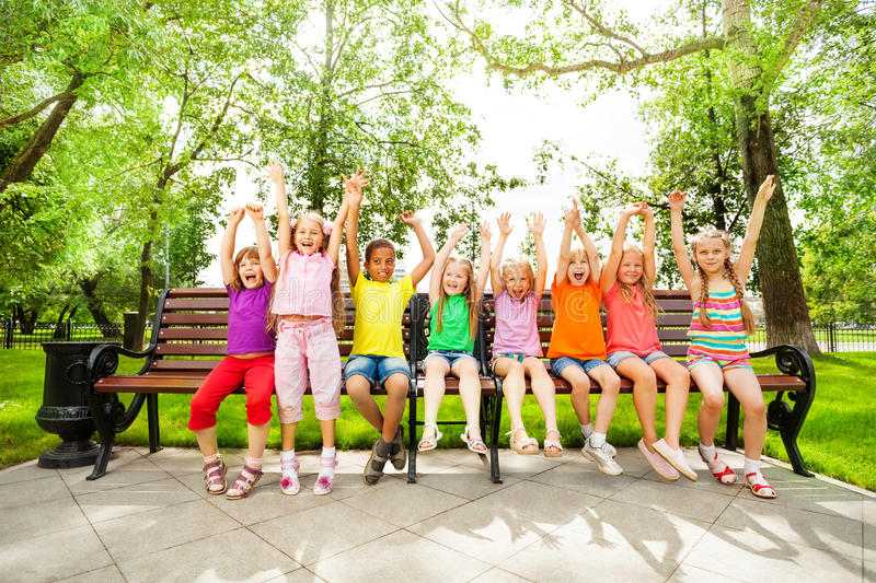 Excited kids with arms and sit in row on bench stock image