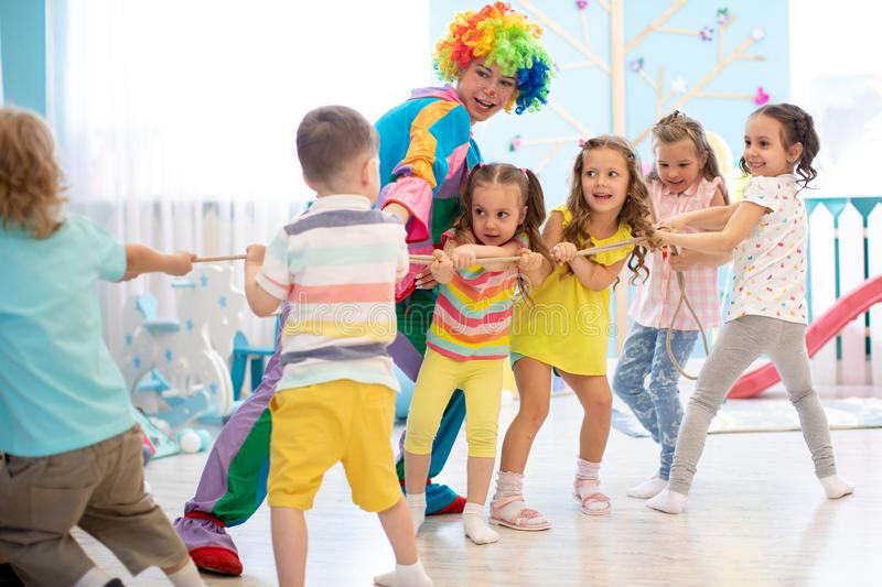 Excited kids playing tug-of-war in club stock photo