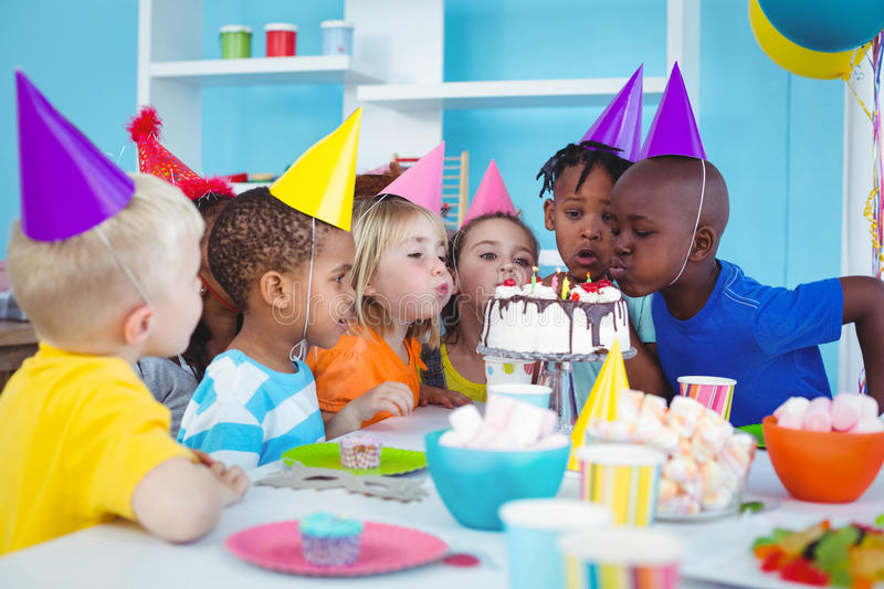Excited kids enjoying a birthday party. Excited kid enjoying a birthday party near the cake royalty free stock photo