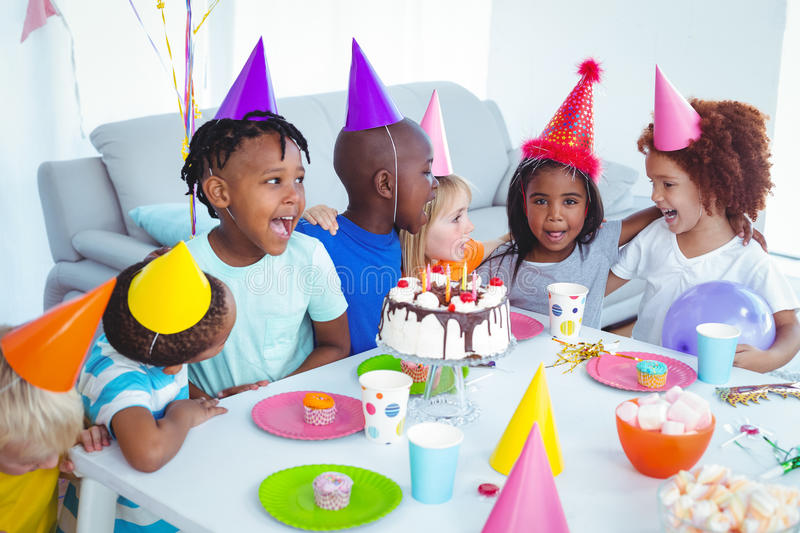 Excited kids enjoying a birthday party. Wearing birthday hats royalty free stock photo