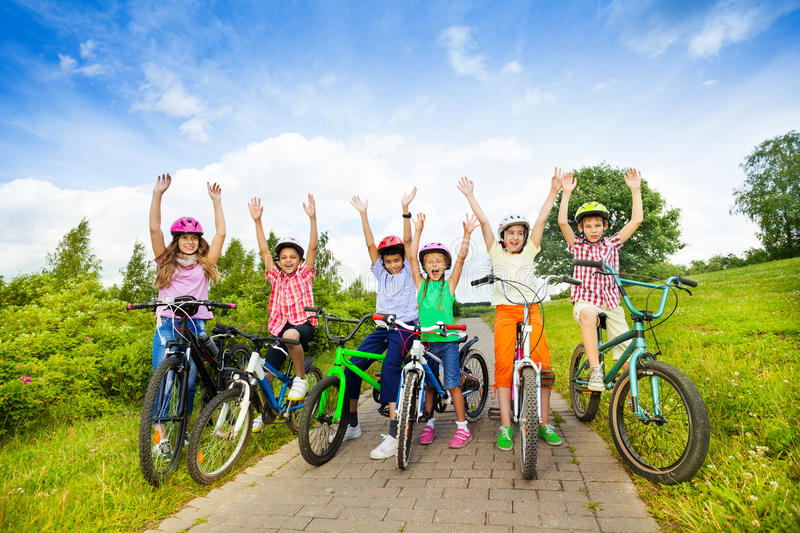 Excited kids in helmets on bikes with hands up stock images