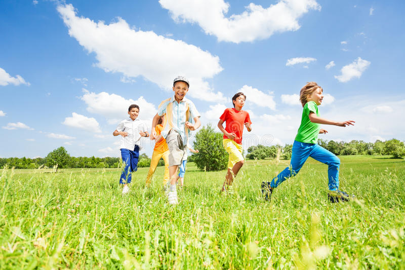 Excited kids playing and running in the field royalty free stock photography