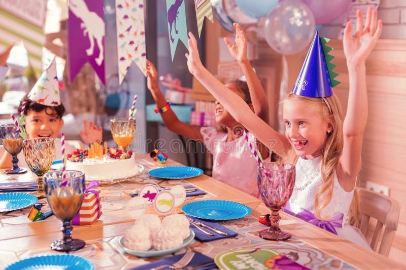 Excited kids putting hands up and dancing at the table stock photos