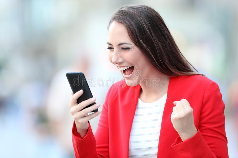 Excited lady celebrating good news checking phone stock photos