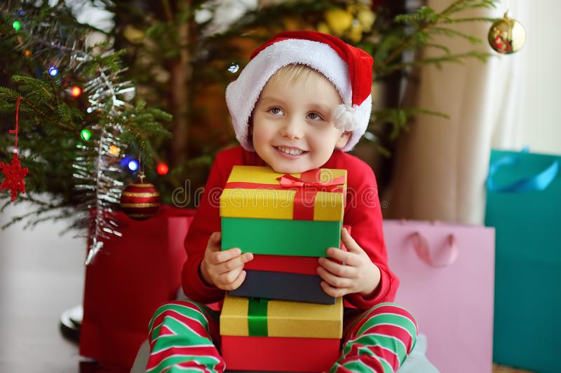 Excited little boy with a Christmas gift under fir tree at home. Portrait of happy kid in Christmas morning royalty free stock photos