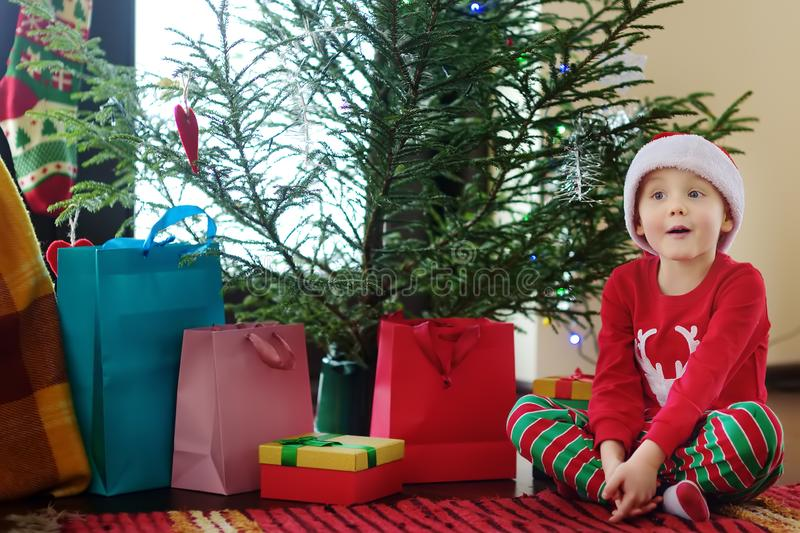Excited little boy with a Christmas gift under fir tree at home. Portrait of happy kid in Christmas morning stock photos