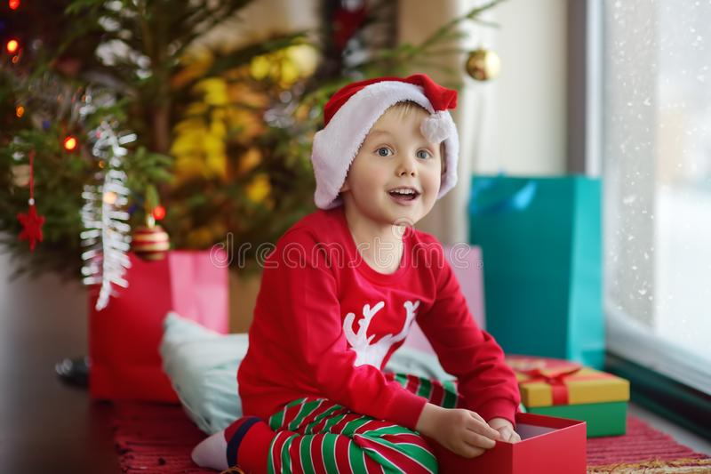 Excited little boy with a Christmas gift under fir tree at home. Portrait of happy kid in Christmas morning stock image
