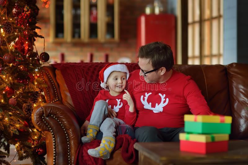 Excited little boy and his father are sitting on sofa with a Christmas gift under fir tree at home. Portrait of happy kid in stock photo