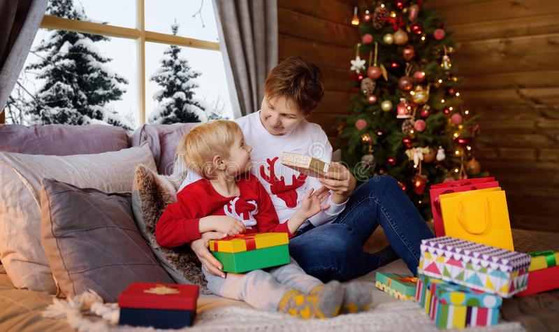 Excited little boy and his mother or grandmother are sitting on bed near a Christmas tree and opening Santa Claus gifts. Family stock photos