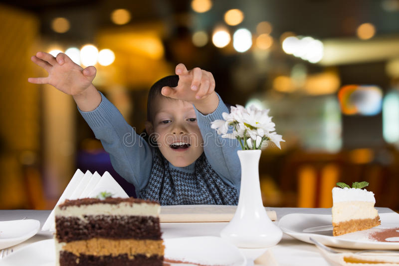Excited little boy reaching for a slice of cake stock photos