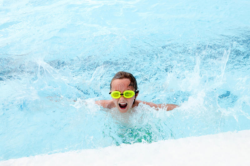 Excited little boy splashing in pool and screaming royalty free stock photos