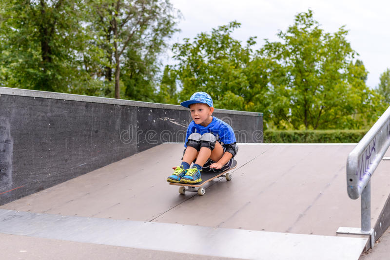 Excited little boy trying out his new skateboard stock photos