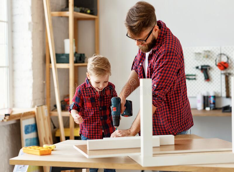Happy kid helping father in carpentry studio stock images