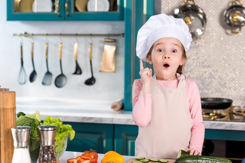 Excited little child in chef hat and apron pointing up with finger and looking at camera. In kitchen royalty free stock images