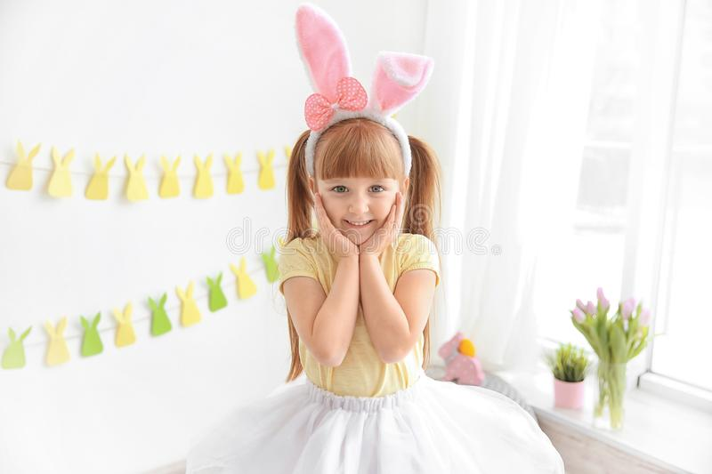 Excited little girl with bunny ears indoors royalty free stock photo