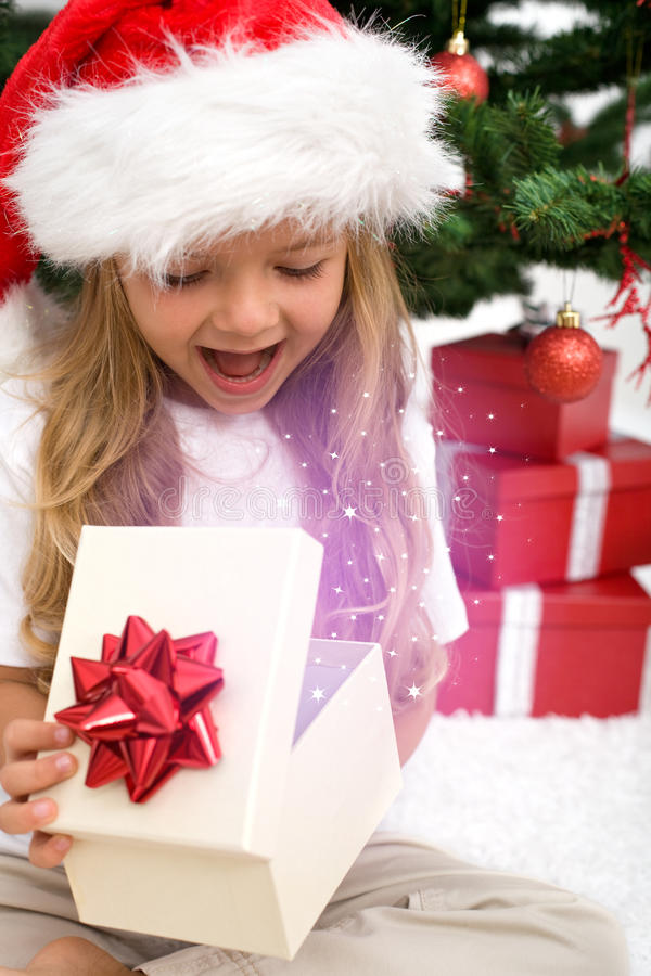 Excited little girl opening christmas present royalty free stock image